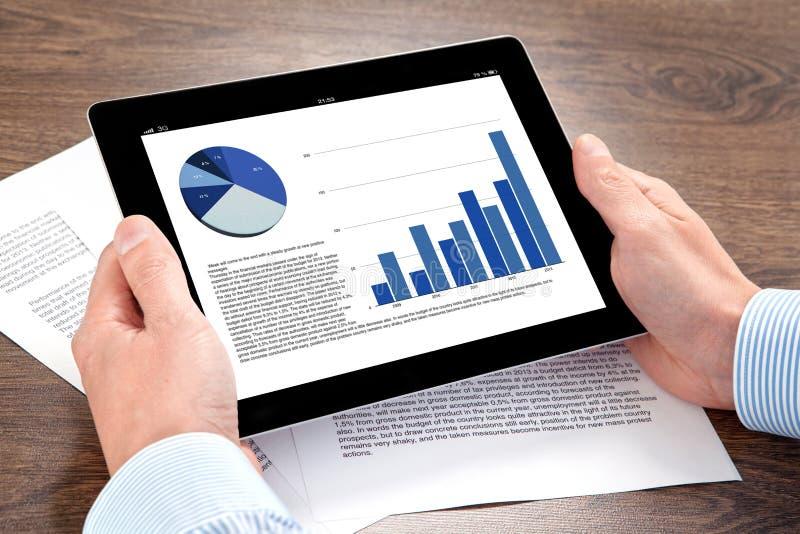 Homem de negócios que guardara uma tabuleta com gráficos em uma tela em Ta imagem de stock royalty free