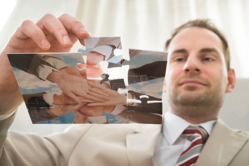 Homem de negócios que introduz a última parte do enigma fotos de stock royalty free