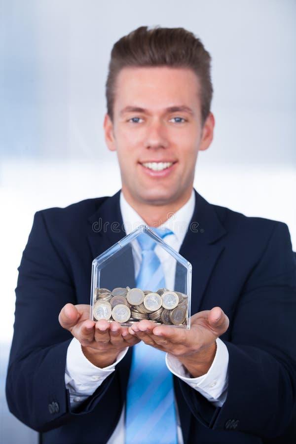 Homem de negócios que introduz a moeda na caixa fotografia de stock royalty free