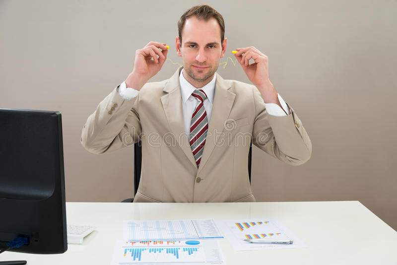 Homem de negócios que introduz o tampão de ouvido nas orelhas imagem de stock royalty free