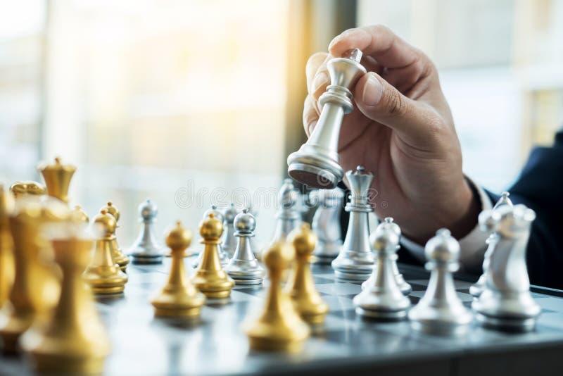 Homem de negócios que joga figuras do jogo de xadrez na tabela de madeira para analy fotografia de stock
