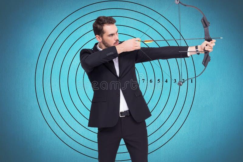 Homem de negócios que joga o tiro ao arco no fundo azul imagens de stock royalty free