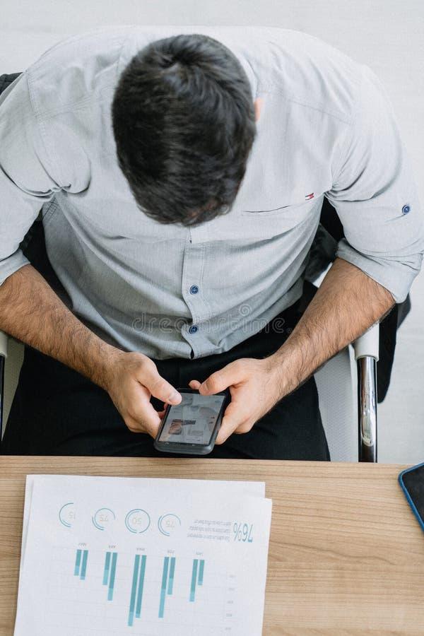 Homem de negócios que joga sua reunião branca do smartphone fotografia de stock royalty free