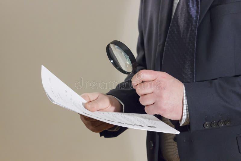 Homem de negócios que lê um original através da lupa imagem de stock
