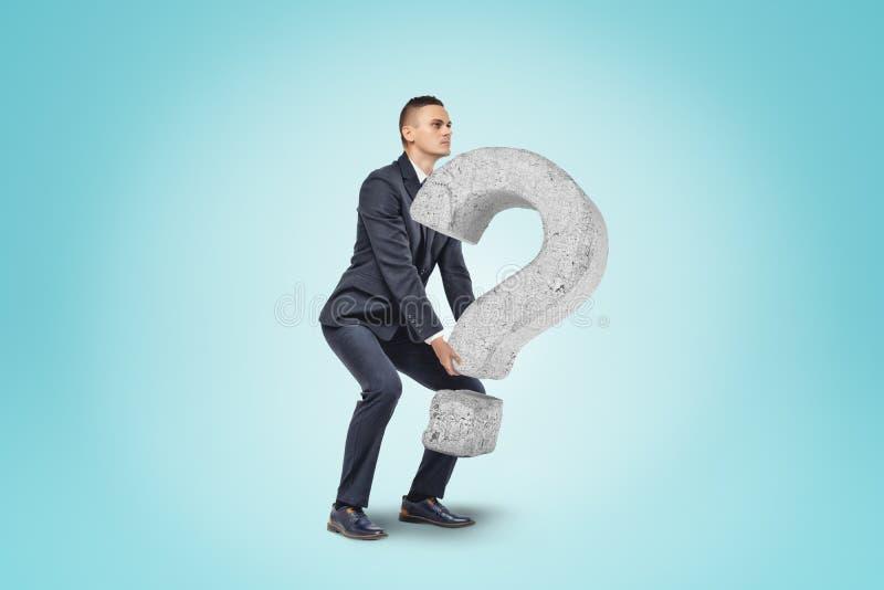 Homem de negócios que levanta acima do ponto de interrogação de pedra grande no fundo azul fotografia de stock royalty free