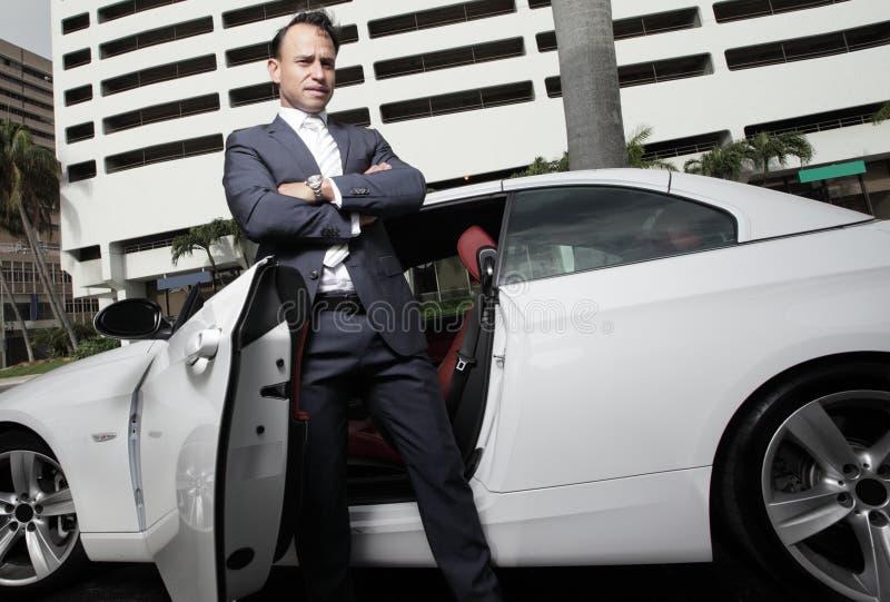 Homem de negócios que levanta por seu carro fotografia de stock