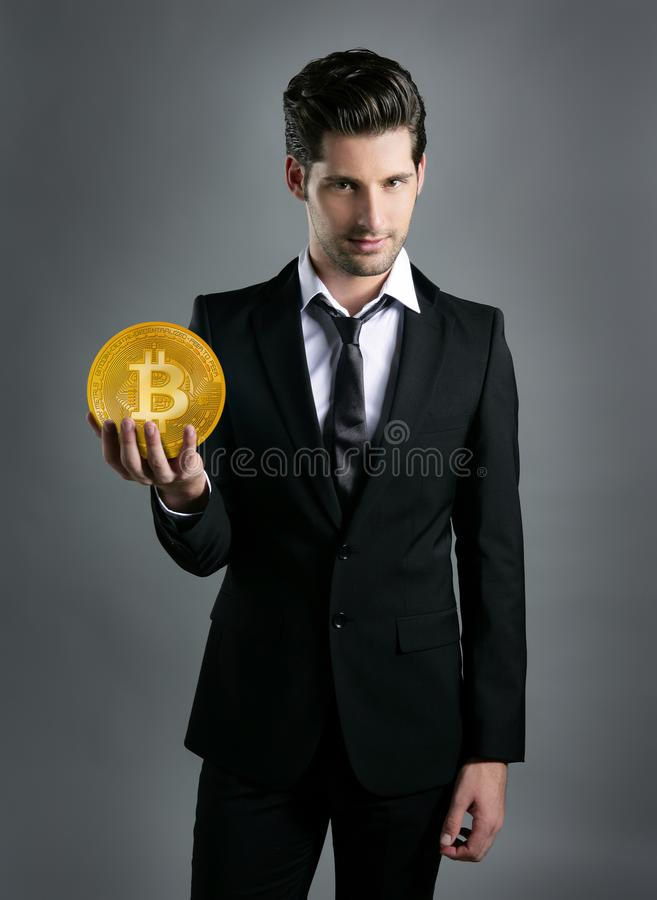 Homem de negócios que mantém a moeda de Bitcoin disponivel imagens de stock
