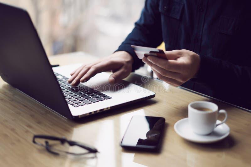 Homem de negócios que mantém o cartão de crédito plástico disponivel e que usa o laptop ao sentar-se na tabela de madeira Fatura  foto de stock royalty free