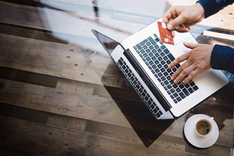 Homem de negócios que mantém o cartão de crédito plástico disponivel e que usa o laptop para a compra em linha ao sentar-se no imagem de stock