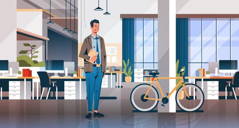Homem de negócios que mantém o escritório criativo do portátil que coworking a bicicleta moderna interior da mesa do local de tra
