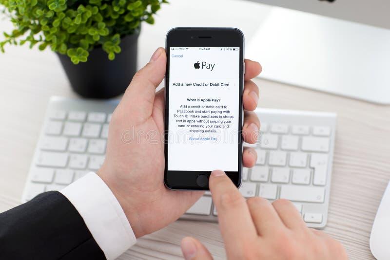 Homem de negócios que mantém o espaço do iPhone 6 cinzento com pagamento de Apple do serviço foto de stock royalty free