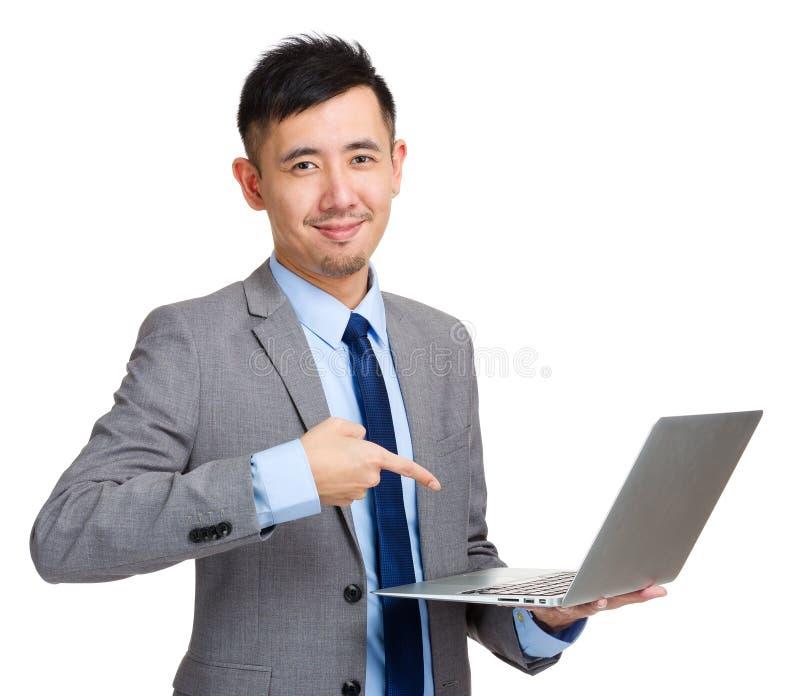 Homem de negócios que mantém o portátil e o dedo que apontam à tela fotos de stock royalty free