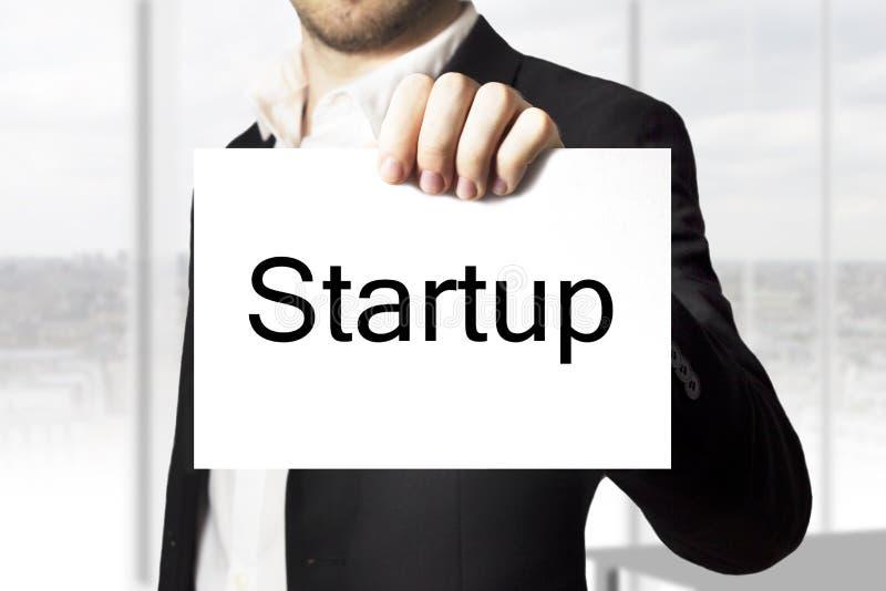 Homem de negócios que mantém o sinal startup foto de stock