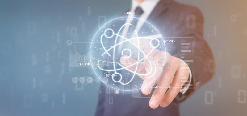 Homem de negócios que mantém um ícone do átomo cercado por dados fotografia de stock