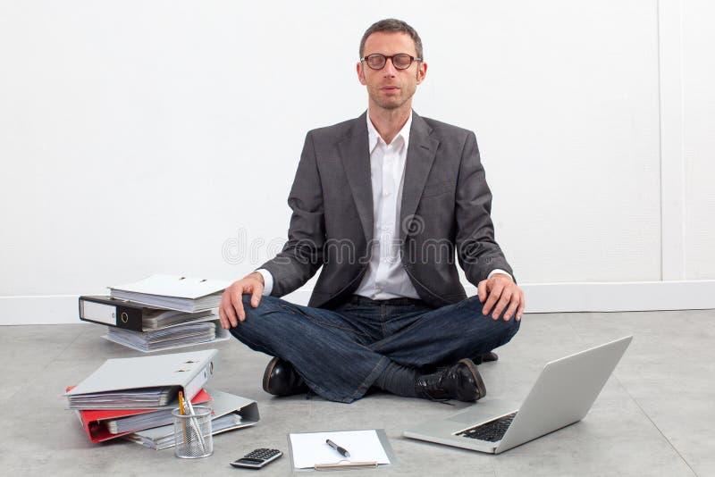 Homem de negócios que medita no escritório que tem a ruptura no trabalho fotos de stock