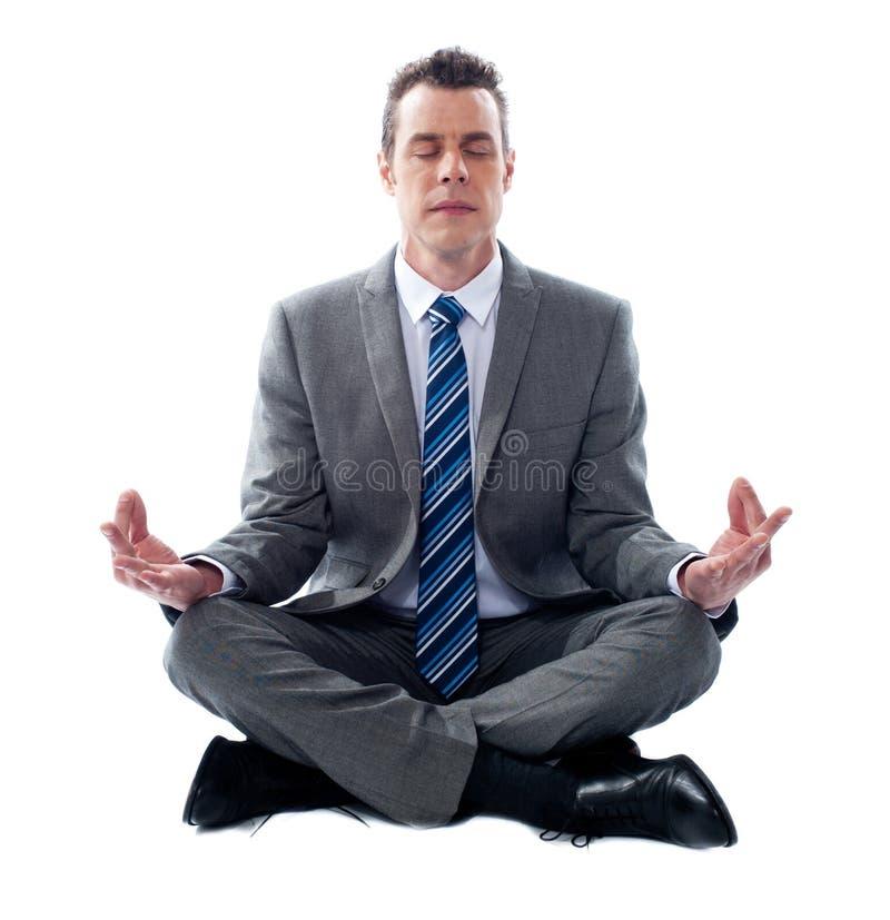 Homem de negócios que meditating na posição de lótus imagens de stock