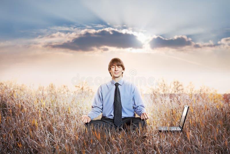 Homem de negócios que meditating no pose dos lótus imagem de stock royalty free
