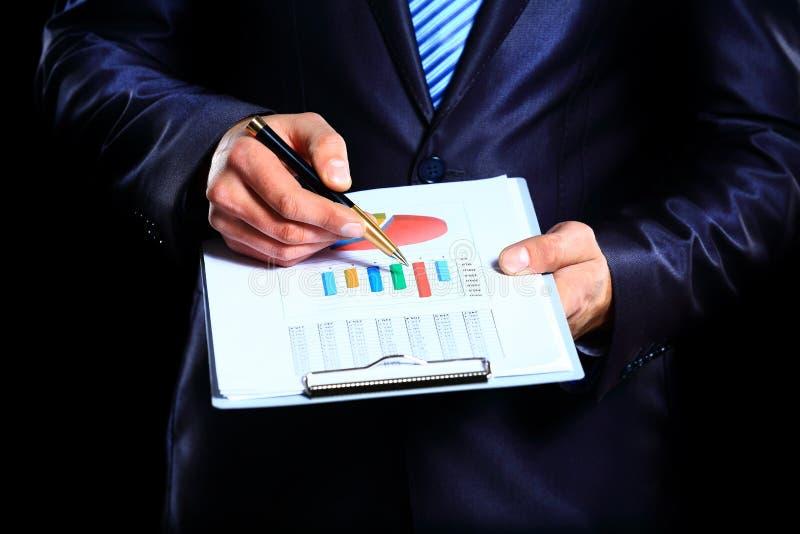 Homem de negócios que monitora o mercado de valores de ação foto de stock