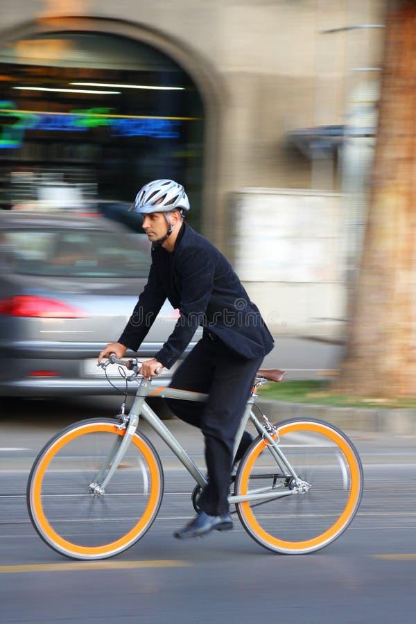Homem de negócios que monta uma bicicleta fotografia de stock
