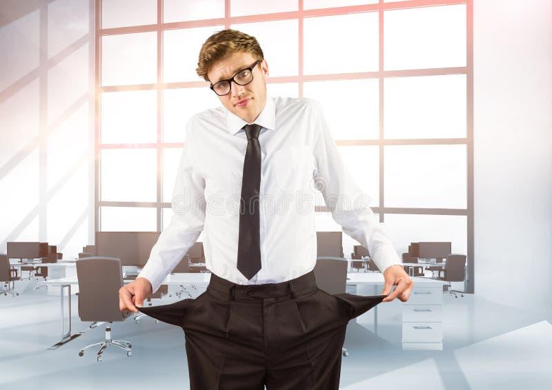 Homem de negócios que mostra bolsos vazios ao estar no escritório imagens de stock royalty free