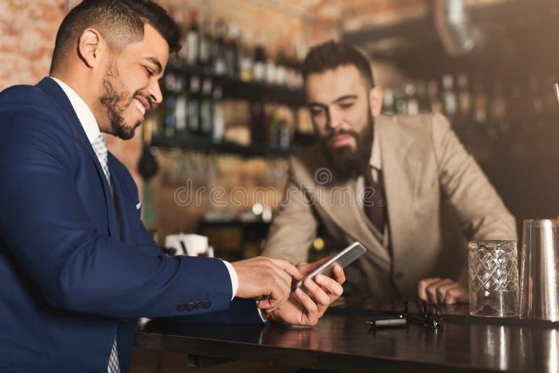 Homem de negócios que mostra a informação no telefone ao empregado de bar fotos de stock