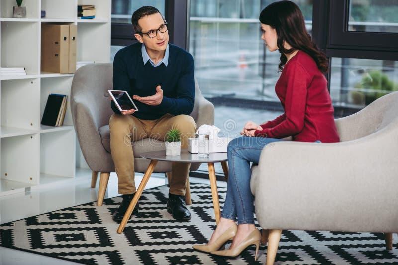 Homem de negócios que mostra a mulher de negócios a tabuleta digital foto de stock royalty free