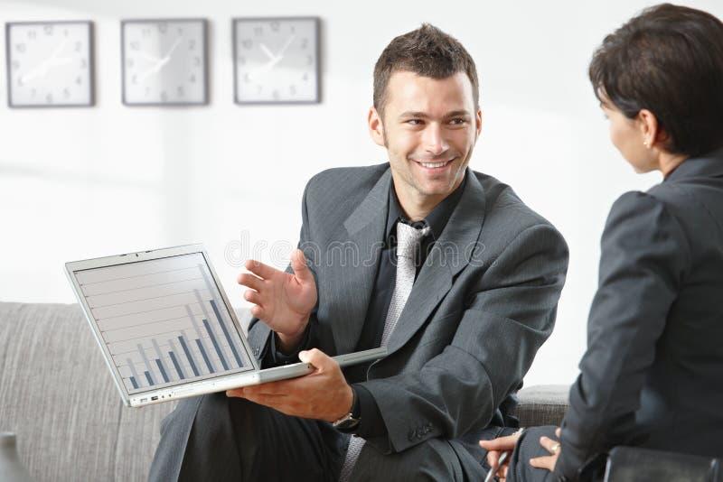 Homem de negócios que mostra o grapth no computador fotos de stock