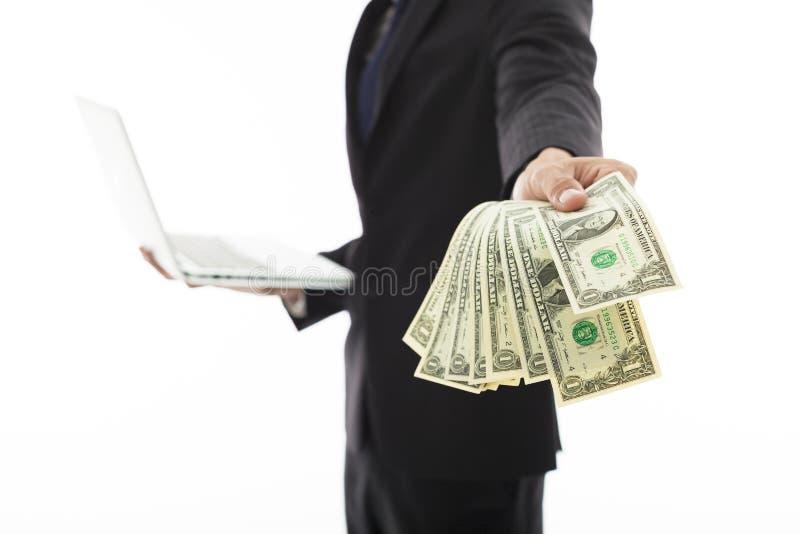 Homem de negócios que mostra o portátil e o dinheiro fotos de stock royalty free