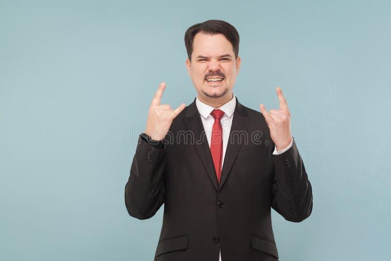 Homem de negócios que mostra o sinal do rock and roll foto de stock