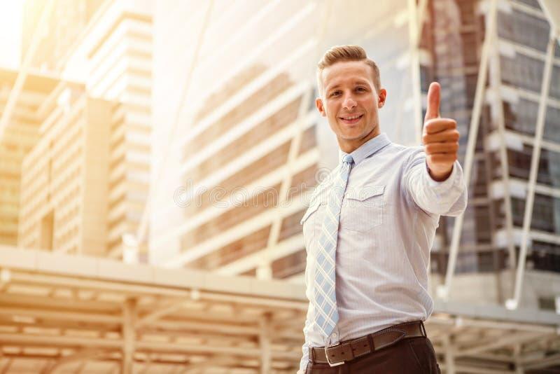 Homem de negócios que mostra os polegares acima do sinal do sucesso fora do escritório na cidade urbana na luz da manhã com espaç foto de stock royalty free