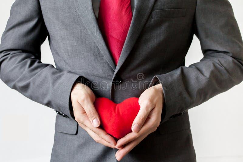 Homem de negócios que mostra a piedade que guarda o coração vermelho em sua caixa imagens de stock royalty free