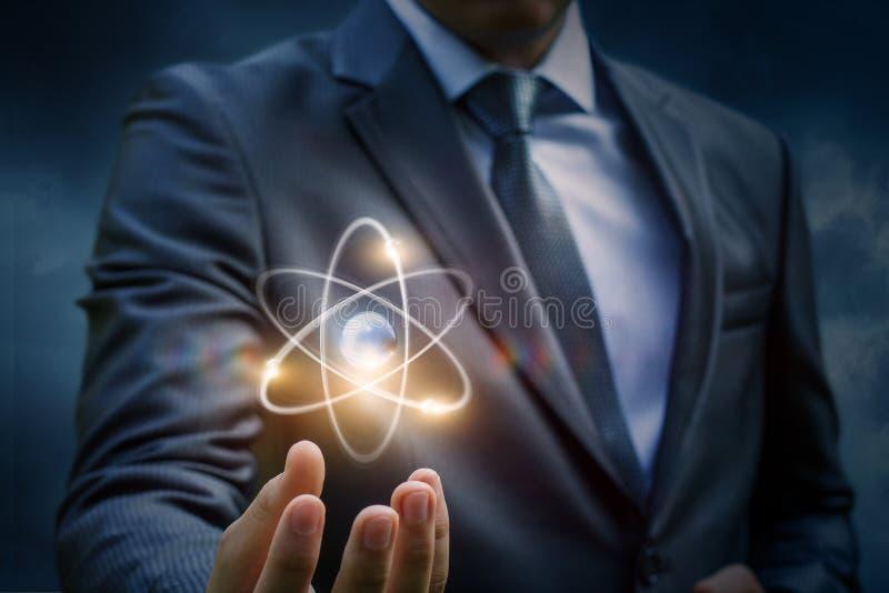 Homem de negócios que mostra um átomo fotos de stock royalty free
