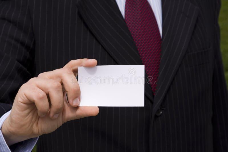 Homem de negócios que mostra um cartão em branco fotografia de stock