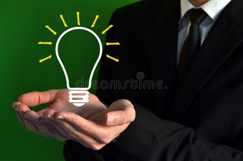 Homem de negócios que mostra um símbolo virtual do bulbo foto de stock