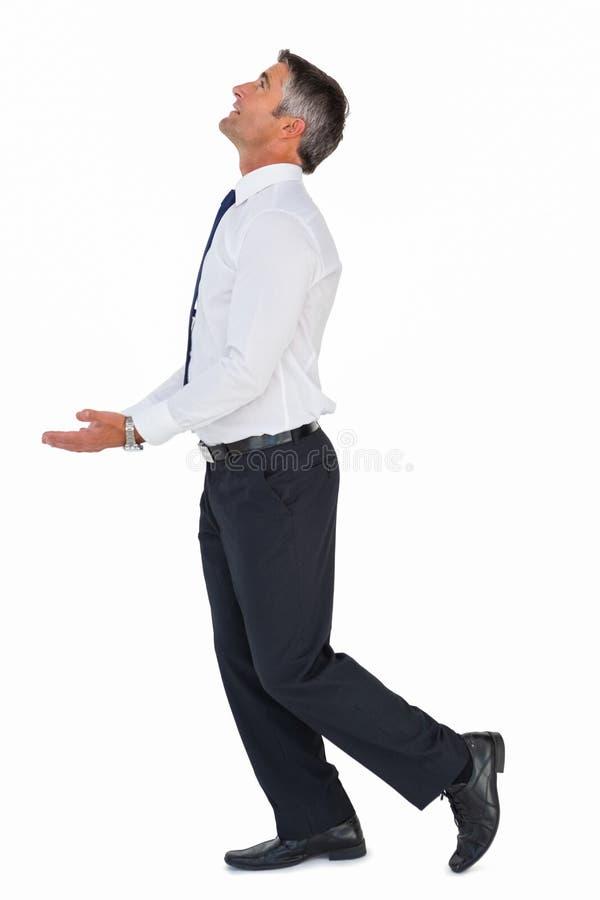 Homem de negócios que olha acima com braços para fora fotografia de stock royalty free