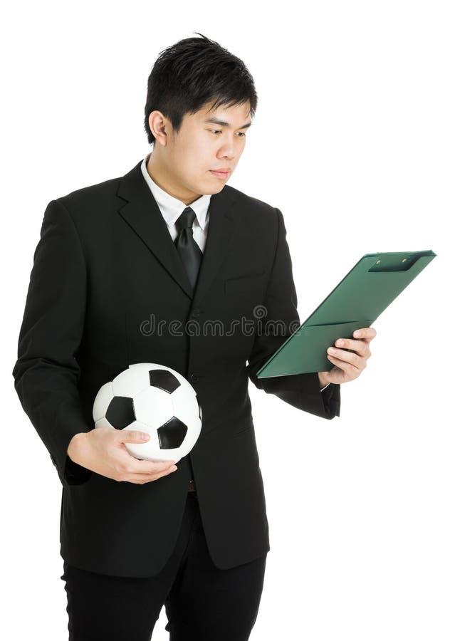 Homem de negócios que olha a almofada do arquivo e que guarda a bola de futebol imagem de stock royalty free