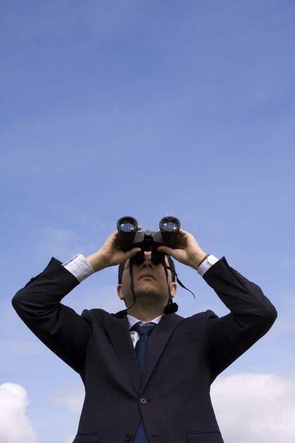 Homem de negócios que olha através dos binóculos imagem de stock royalty free