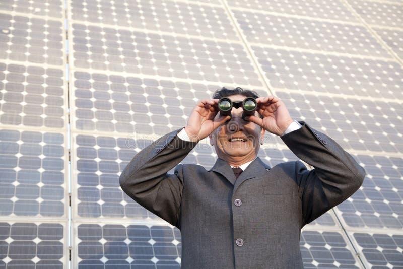 Homem de negócios que olha através dos binóculos na frente dos painéis solares foto de stock royalty free