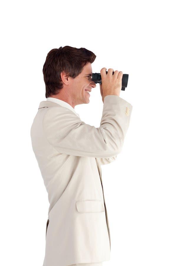 Homem de negócios que olha com binóculos imagem de stock