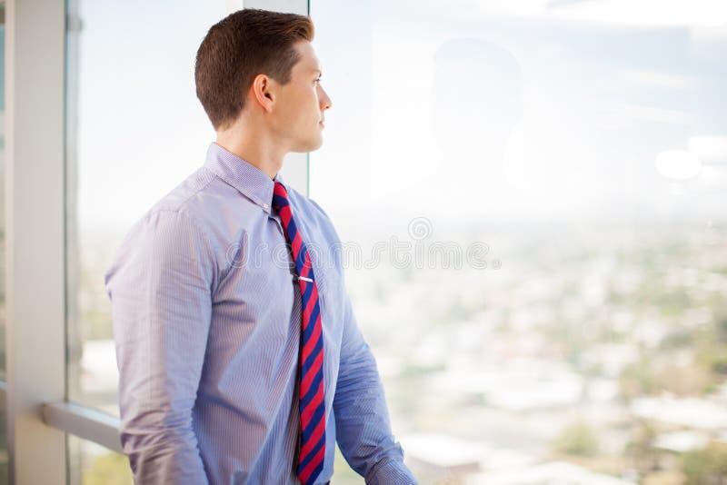 Homem de negócios que olha a janela imagens de stock royalty free