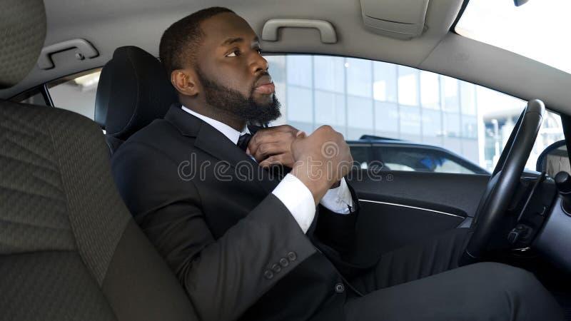 Homem de negócios que olha no espelho retrovisor, ajustando o laço, nervoso antes da entrevista imagem de stock