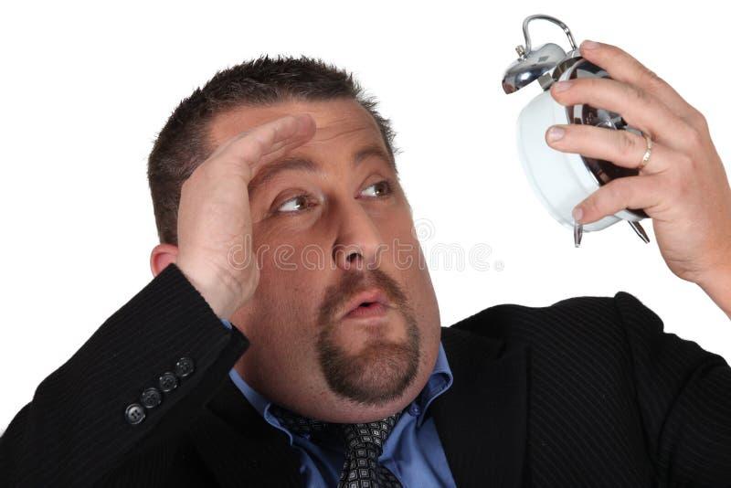 Homem de negócios que olha o despertador imagem de stock