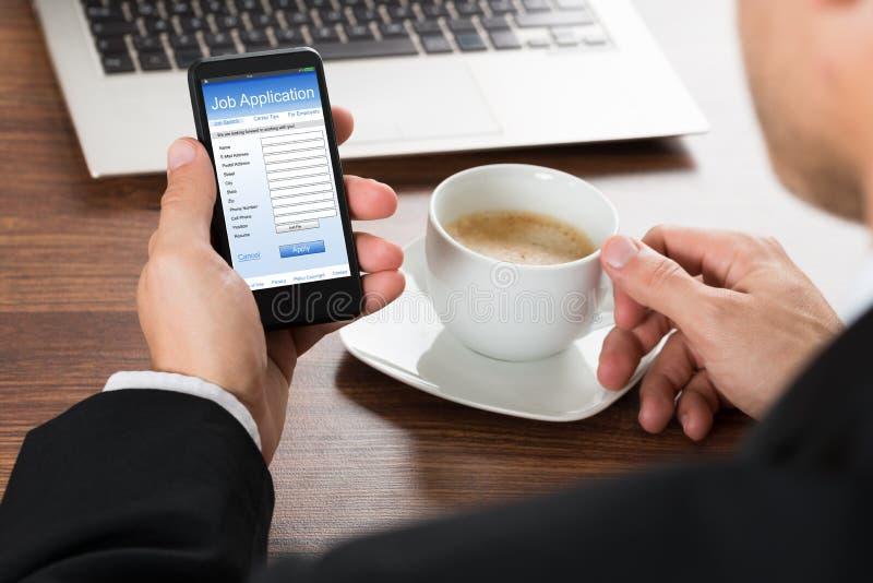 Homem de negócios que olha o formulário de candidatura a cargo no telefone celular foto de stock