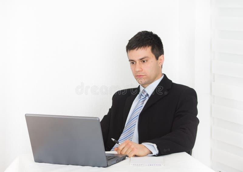 Homem de negócios que olha o portátil imagem de stock royalty free