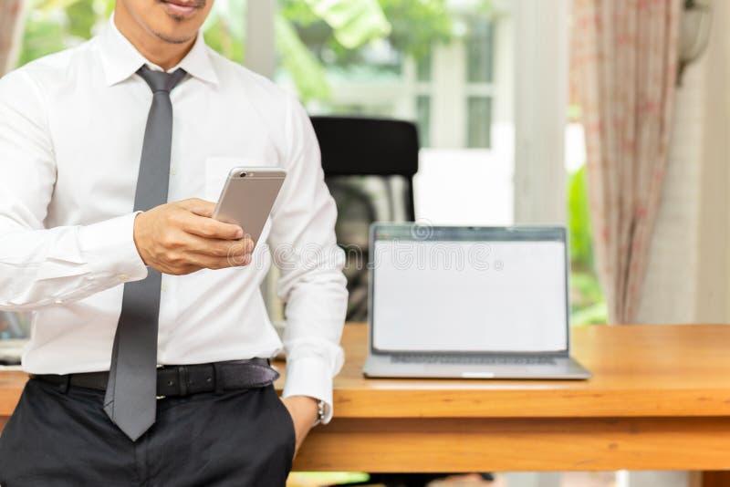 Homem de negócios que olha o telefone celular com o portátil na tabela de madeira no escritório imagens de stock royalty free