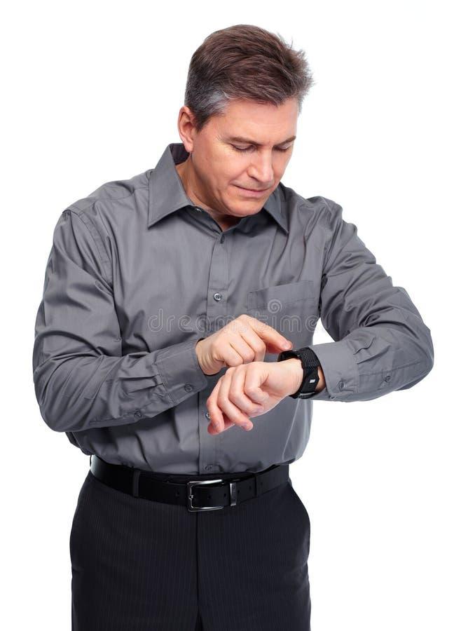 Homem de negócios que olha o tempo em seu relógio foto de stock