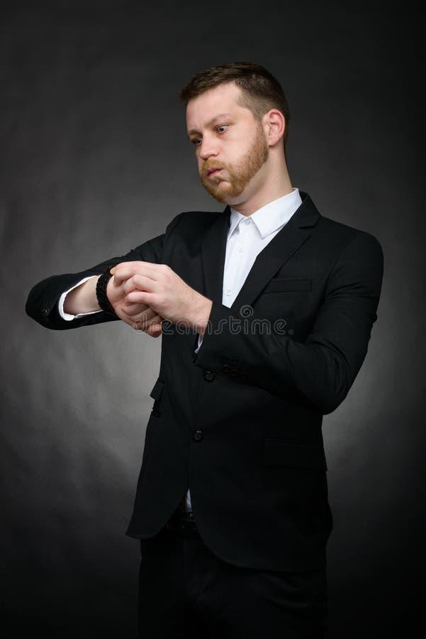 Homem de negócios que olha preocupado no relógio fotografia de stock