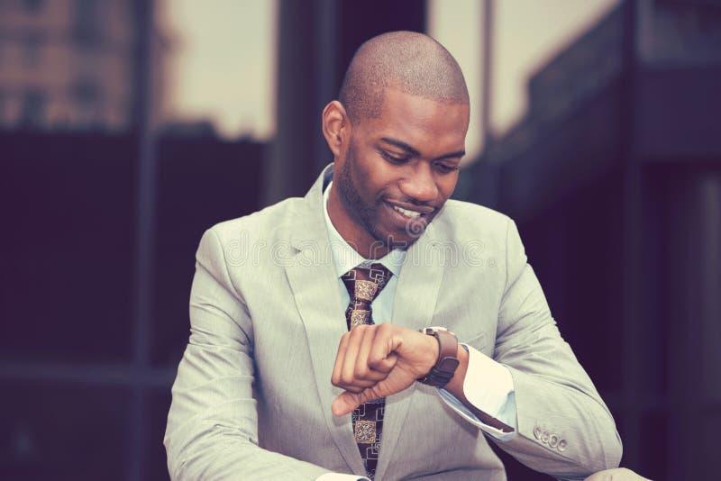 Homem de negócios que olha seu relógio que senta-se fora fotografia de stock