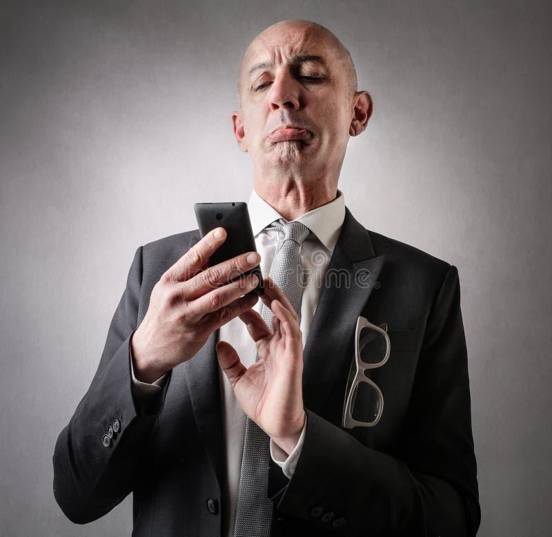 Homem de negócios que olha seu telefone fotografia de stock