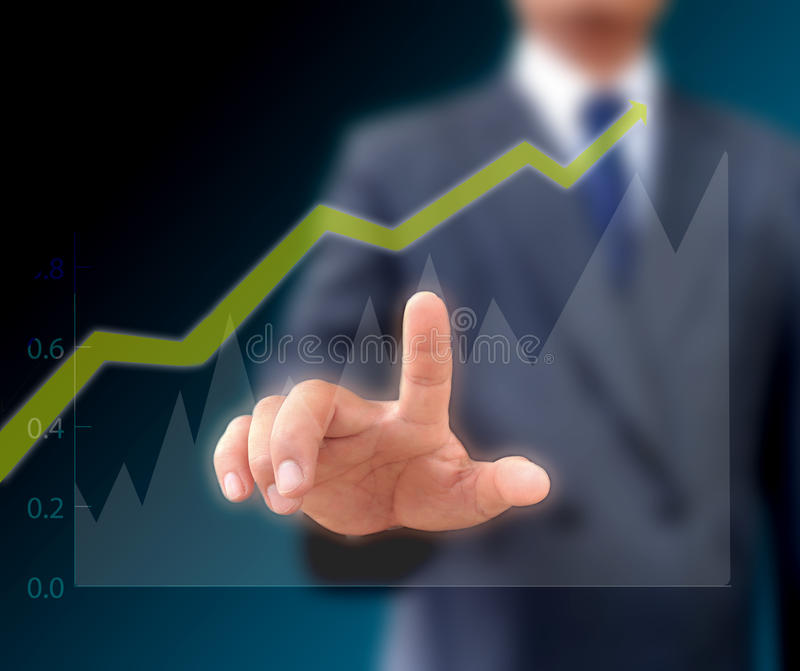 Homem de negócios que olha a tendência ascendente de uma carta gráfica. fotografia de stock